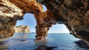 La cueva de los Arcos o cueva Moraig se encuentra en el extremo derecho de la cala Moraig, se trata de la salida al mar del curso de agua subterránea mas largo de España, y es un lugar frecuentado por espeleologos y buceadores.